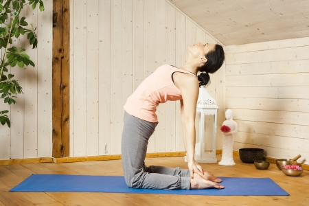 An image of a pretty woman doing yoga at home - Ushtrasana Stock Photo - 18687646