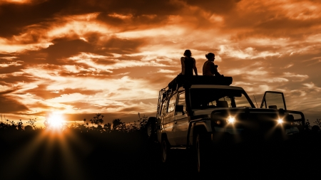 4 wheel: 2 women sitting on their car and watching the sunset Stock Photo