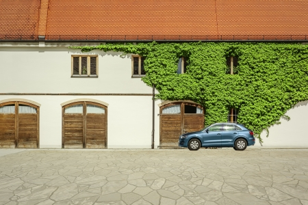 crossover: An image of a SUV car in front of a big house with a wine plant