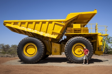 An image of a big yellow transporter and a man in front of a wheel photo