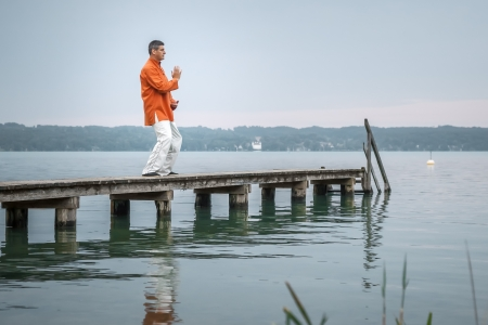 A man doing Qi-Gong in the early morning at the lake Starnberg Stock Photo - 21054148