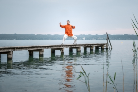 qigong: A man doing Qi-Gong in the early morning at the lake Starnberg