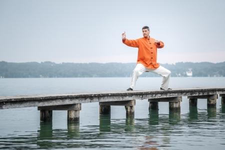 Un uomo che fa Qi-Gong la mattina presto presso il lago di Starnberg Archivio Fotografico - 21054153