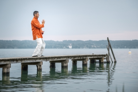 tai chi: A man doing Qi-Gong in the early morning at the lake Starnberg