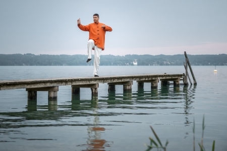 taichi: A man doing Qi-Gong in the early morning at the lake Starnberg