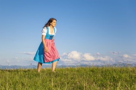A woman in bavarian traditional dirndl in the nature photo