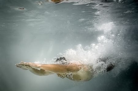 An image of a man diving in the pool with lots of air bubbles photo