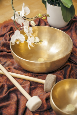singing bowl massage: An image of some singing bowls and a white orchid