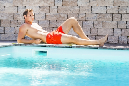 An image of a handsame man relaxing at the pool photo
