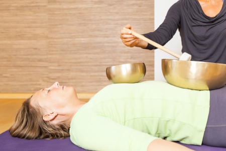 A woman is relaxing with singing bowls on her body Stock Photo