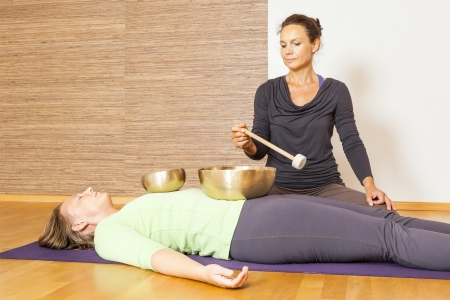 A woman is relaxing with singing bowls on her body Stock Photo - 21851270