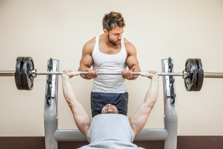 weight weightlifting: A handsome young muscular sports man doing weight lifting and gets help from his friend Stock Photo