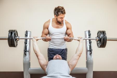 levantando pesas: Un joven deportes muscular hermoso que hace el levantamiento de pesas y obtiene ayuda de su amigo