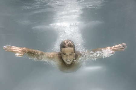 An image of a man diving in a pool Stock Photo