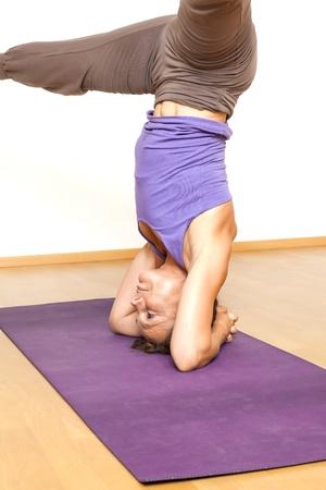 An image of a pretty woman doing yoga - Salamba Shirshasana Head Stand photo