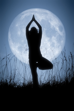 An image of a pretty woman doing yoga under a big pale moon photo
