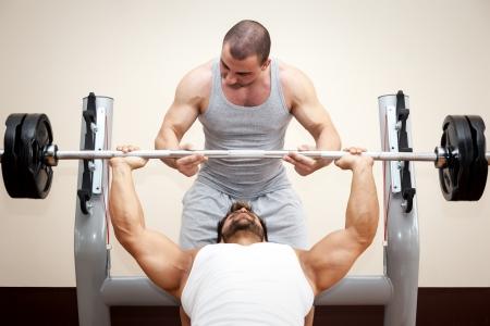 levantar pesas: Un apuesto joven deportes muscular que hace press de banca con un poco de ayuda Foto de archivo