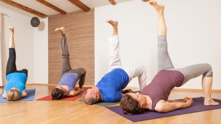 An image of some people doing yoga exercises - Eka Pada Setu Bandha Sarvangasana  photo