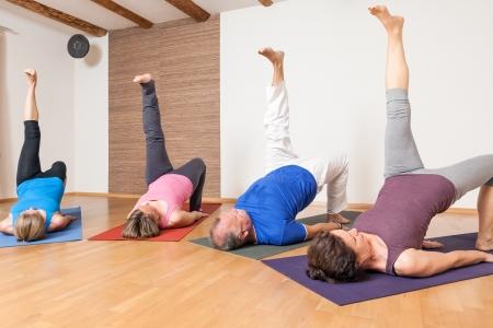 L'immagine di alcune persone che fanno esercizi di yoga - Eka Pada Setu Bandha Sarvangasana Archivio Fotografico - 24733111
