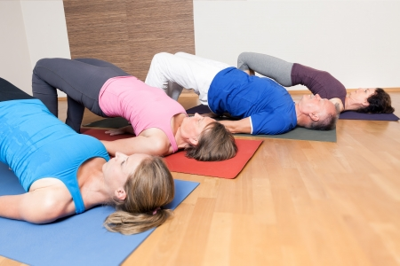 An image of some people doing yoga exercises - Setu Bandha Sarvangasana Stock Photo - 24733114