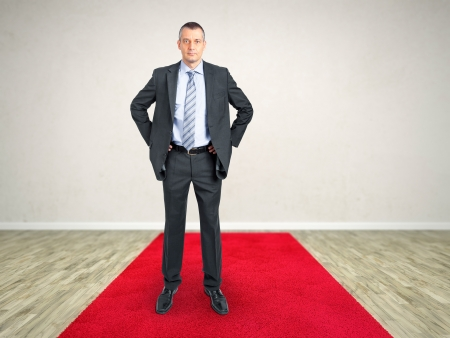 A room with a red carpet and a business man photo