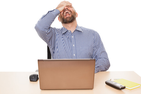 A crying man in front of his PC isolated on white background