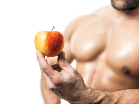 An image of a handsome young muscular sports man and a apple photo