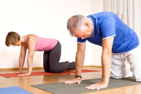 Een beeld van een aantal mensen die yoga-oefeningen