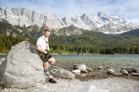 zugspitze mountain: A traditional bavarian man at lake Eibsee with the Zugspitze mountain  Stock Photo