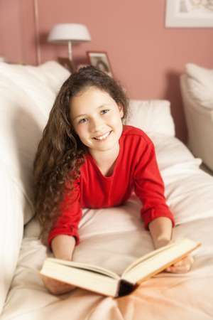An image of a girl with a book on the sofa photo