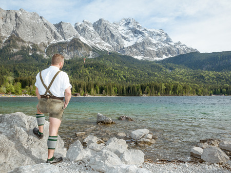zugspitze mountain: A traditional bavarian man at lake Eibsee with the Zugspitze mountain in the background
