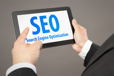 A business man pointing to a tablet pc with the message Search Engine Optimization photo
