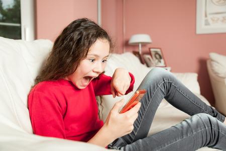 niños platicando: Una imagen de una chica joven con un teléfono móvil