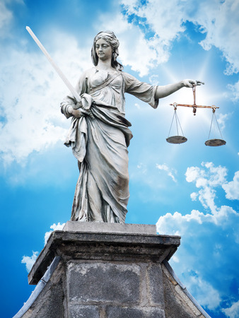An image of a beautiful justitia statue in front of a blue sky photo