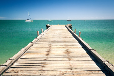 old pier: An image of the wooden jetty at Monkey Mia Australia Stock Photo
