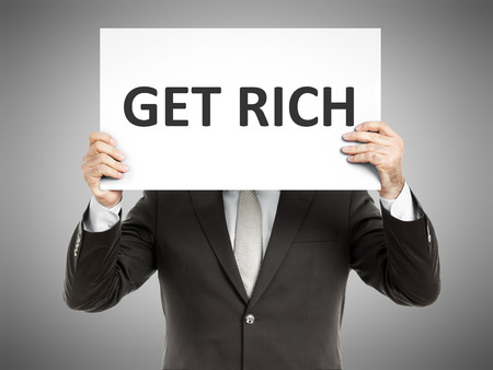 A business man holding a paper in front of his face with the text get rich photo