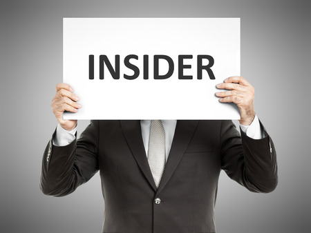 A business man holding a paper in front of his face with the text insider Stockfoto