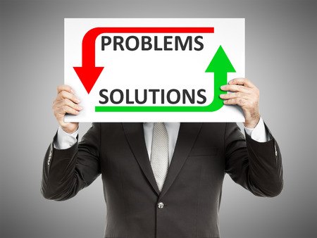 A business man holding a paper in front of his face with the text problems solutions photo