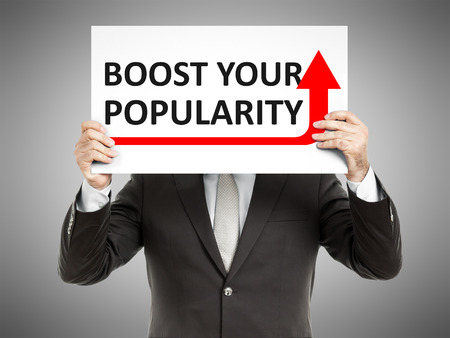 popularity: A business man holding a paper in front of his face with the text boost your popularity Stock Photo