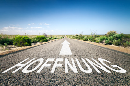 An image of a road to the horizon with text hope in german language photo