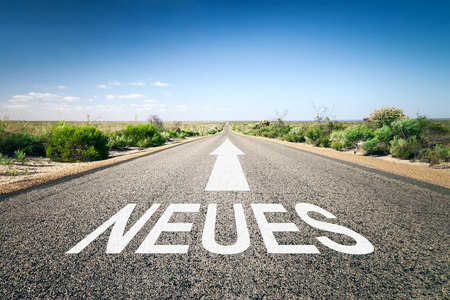 An image of a road to the horizon with text new in german language photo
