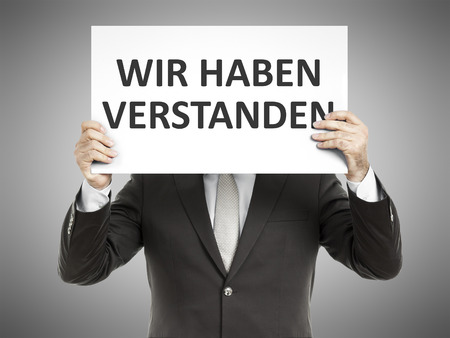 understood: A business man holding a paper in front of his face with the message we understood in german language