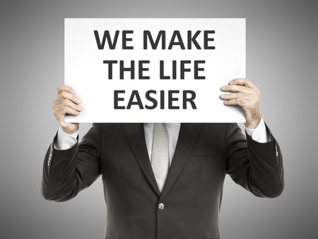 easier: A business man holding a paper in front of his face with the message we make the life easier