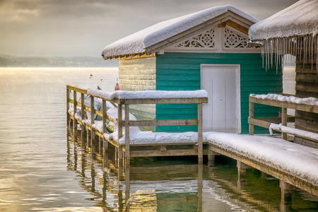 An image of the lake huts in Tutzing Bavaria Germany at winter sunrise