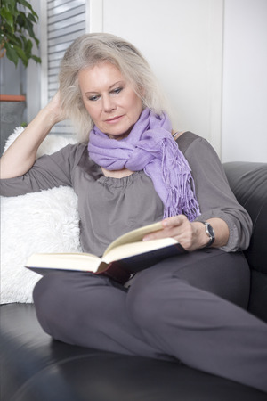 An image of a beautiful woman reading a book on her sofa photo