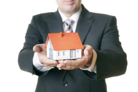 An image of a man holding a house in his hands photo