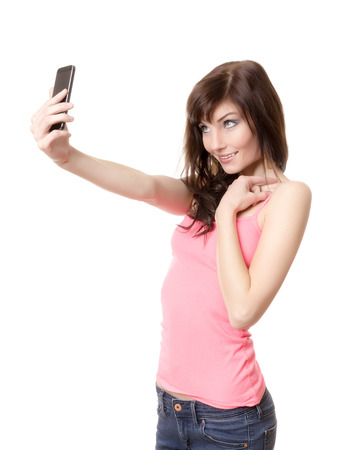 A girl is making a photograph of herself with a smartphone photo