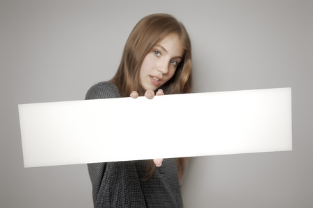 An image of a beautiful teenage girl holding a white board photo