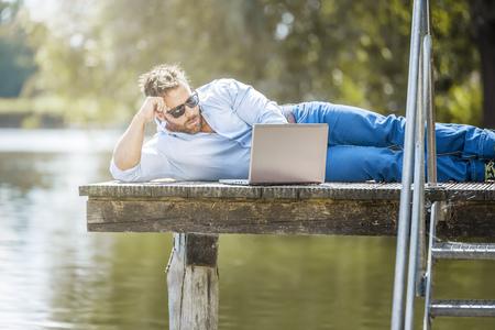 libertad: Un hombre con su portátil está trabajando al aire libre en el lago