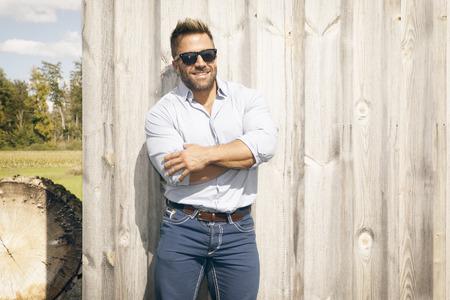 madera rústica: Un hombre guapo al aire libre delante de una pared de fondo de madera